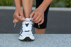 tying-laces-closeup-female-hands-running-shoes-wall-training
